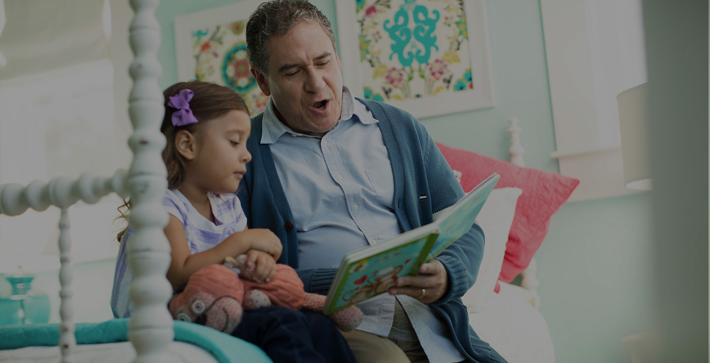A digestive tract cancer survivor reads a story book to his daughter while sitting on a bed
