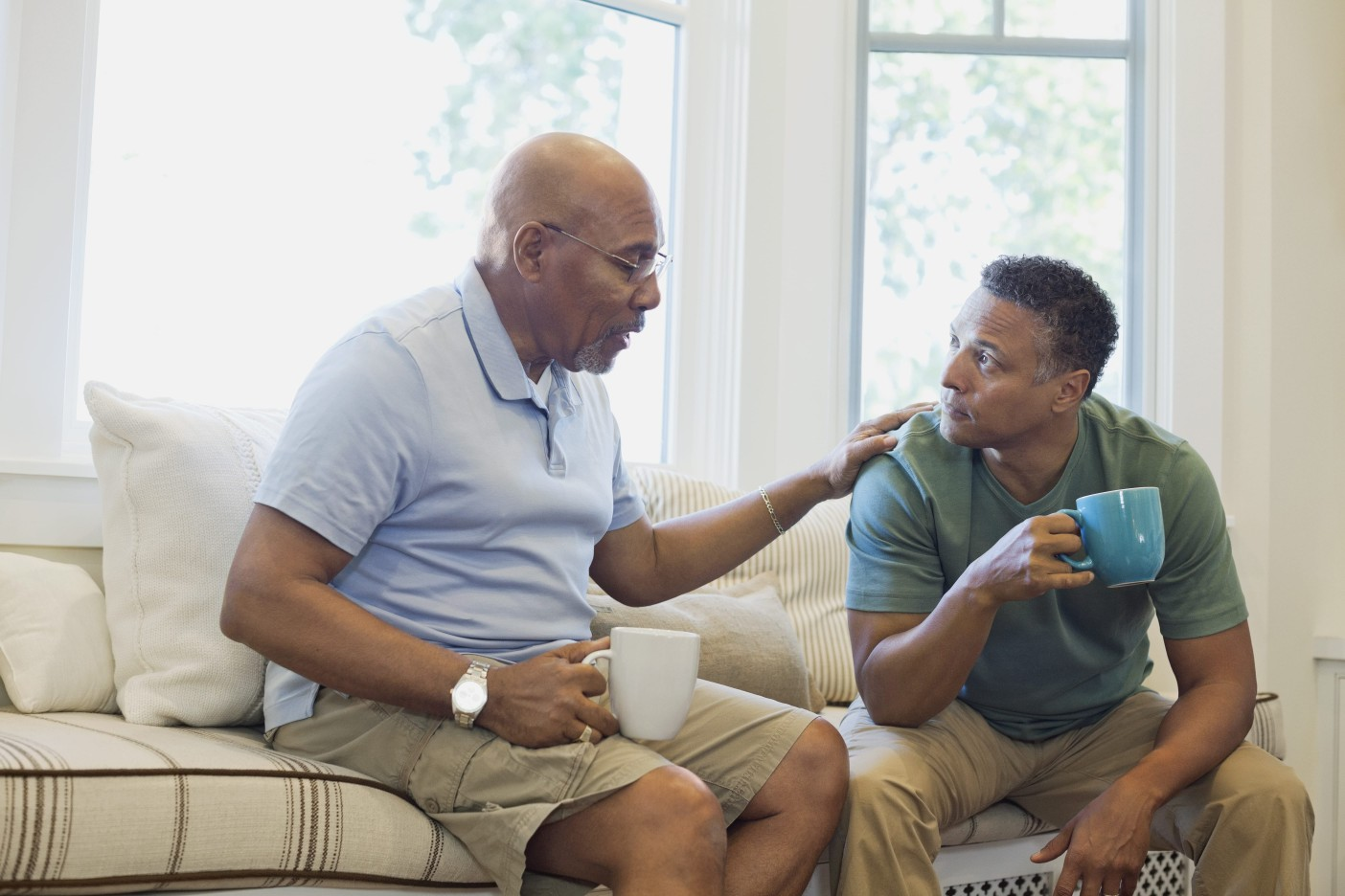 Two men sit in a well-lit living room and discuss bone marrow transplant support groups while drinking coffee
