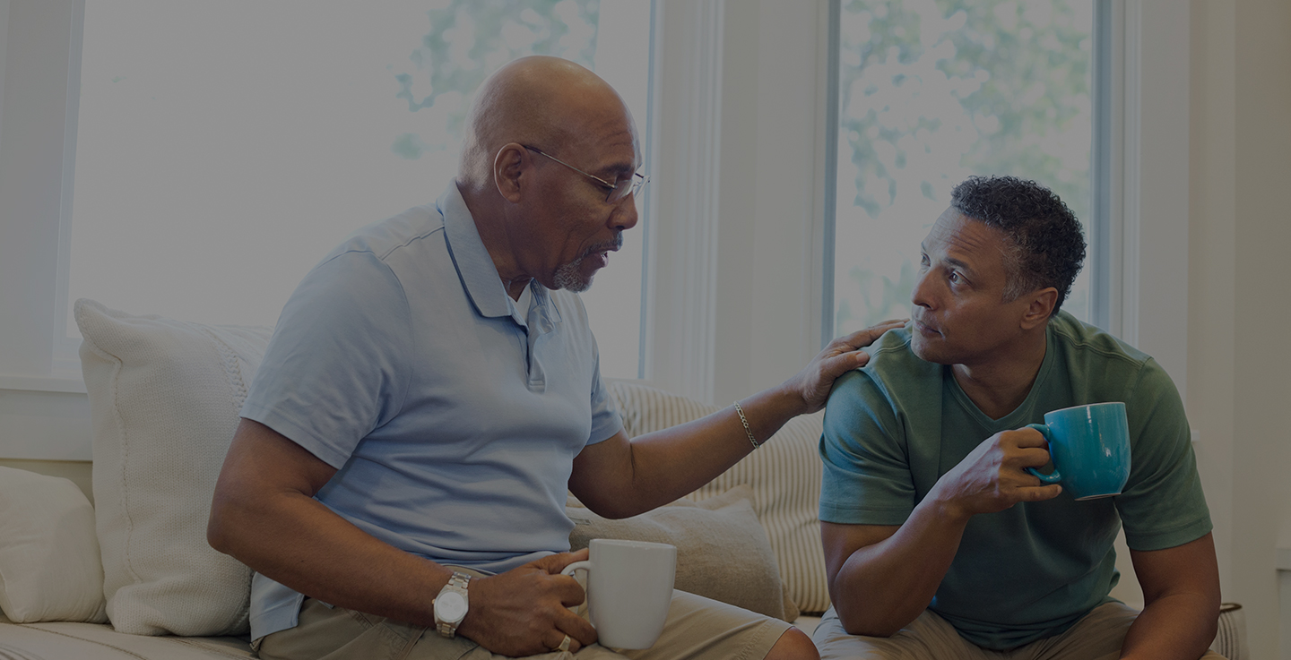 Two men sit in a well-lit living room and discuss cancer care support groups while drinking coffee