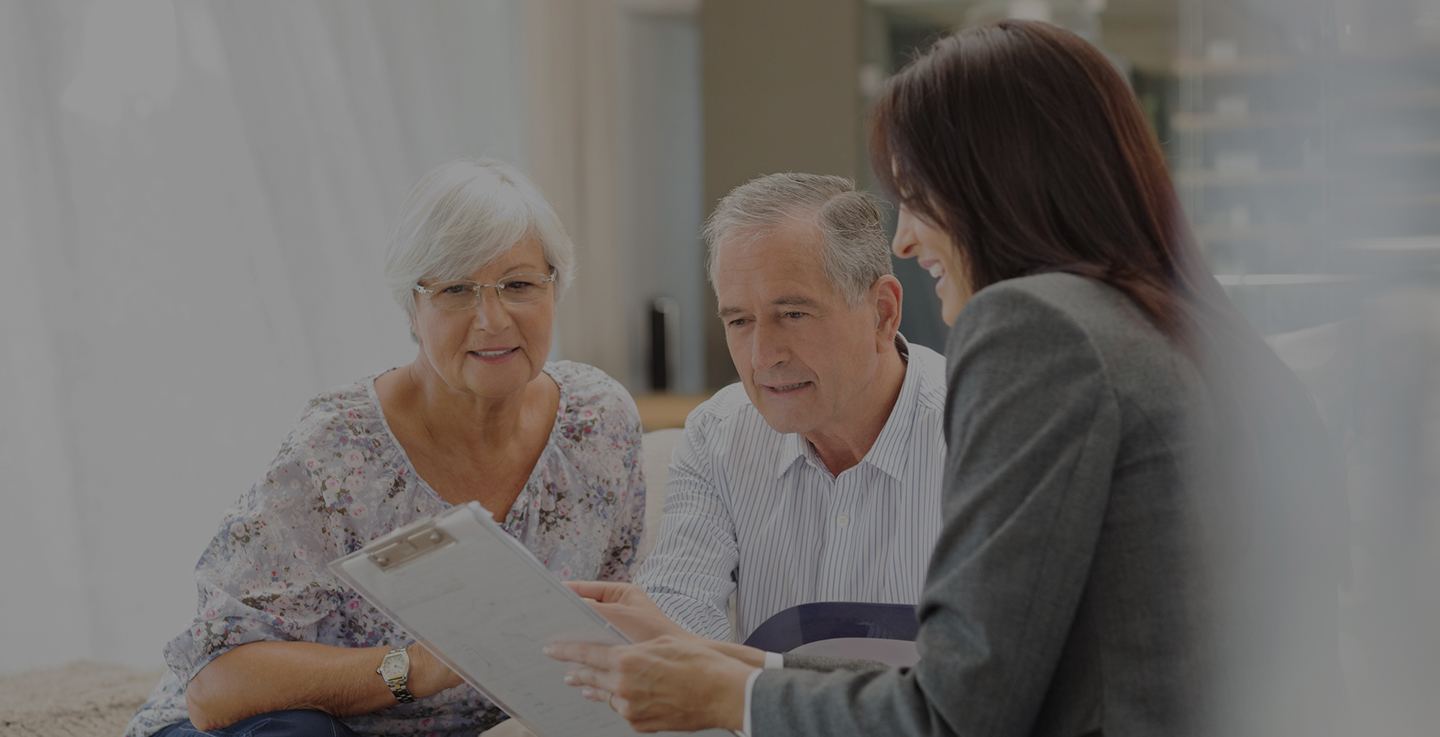 An elderly couple discuss financial assistance for cancer care with a financial planning specialist