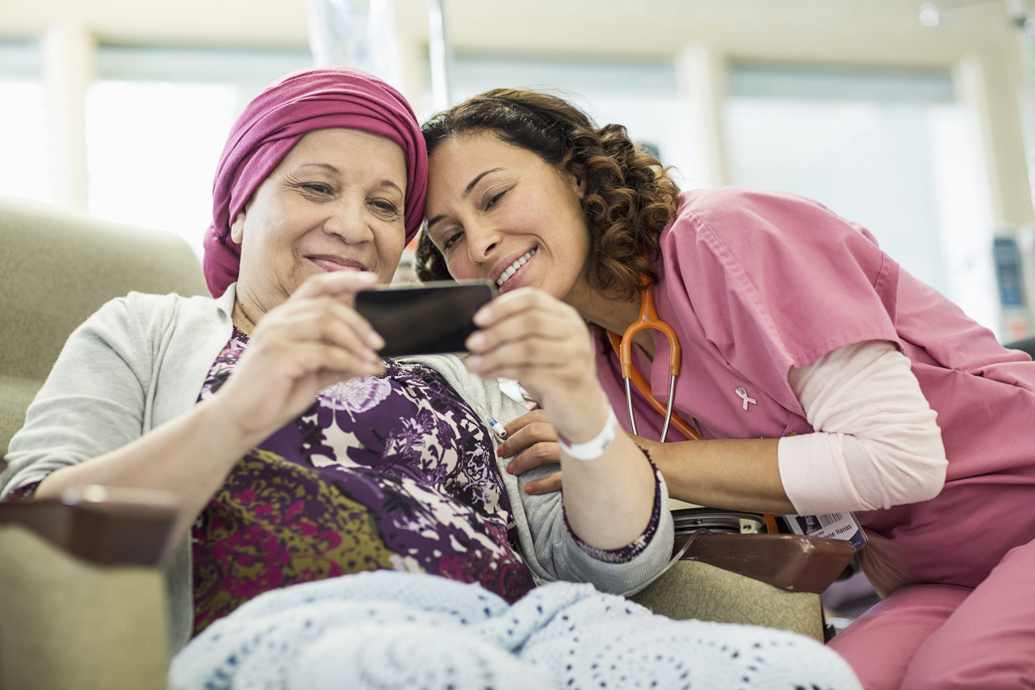 A patient receiving chemotherapy and a cancer treatment specialist smile as they look at photos on a phone together