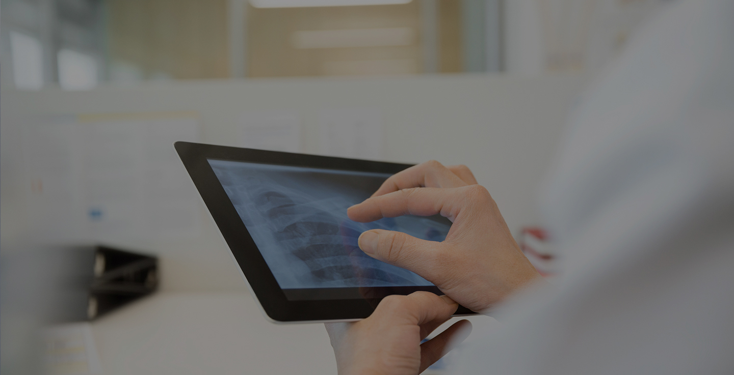 An immunotherapy specialists reviews a cancer patient's imaging scans on a tablet