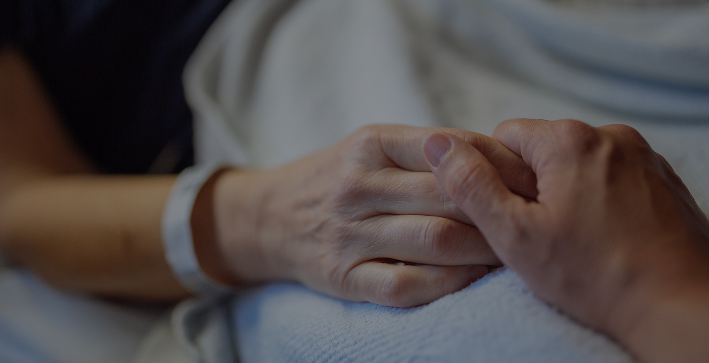 A cancer patient wearing a hospital bracelet holds hands with a loved one at AdventHealth Cancer Institute
