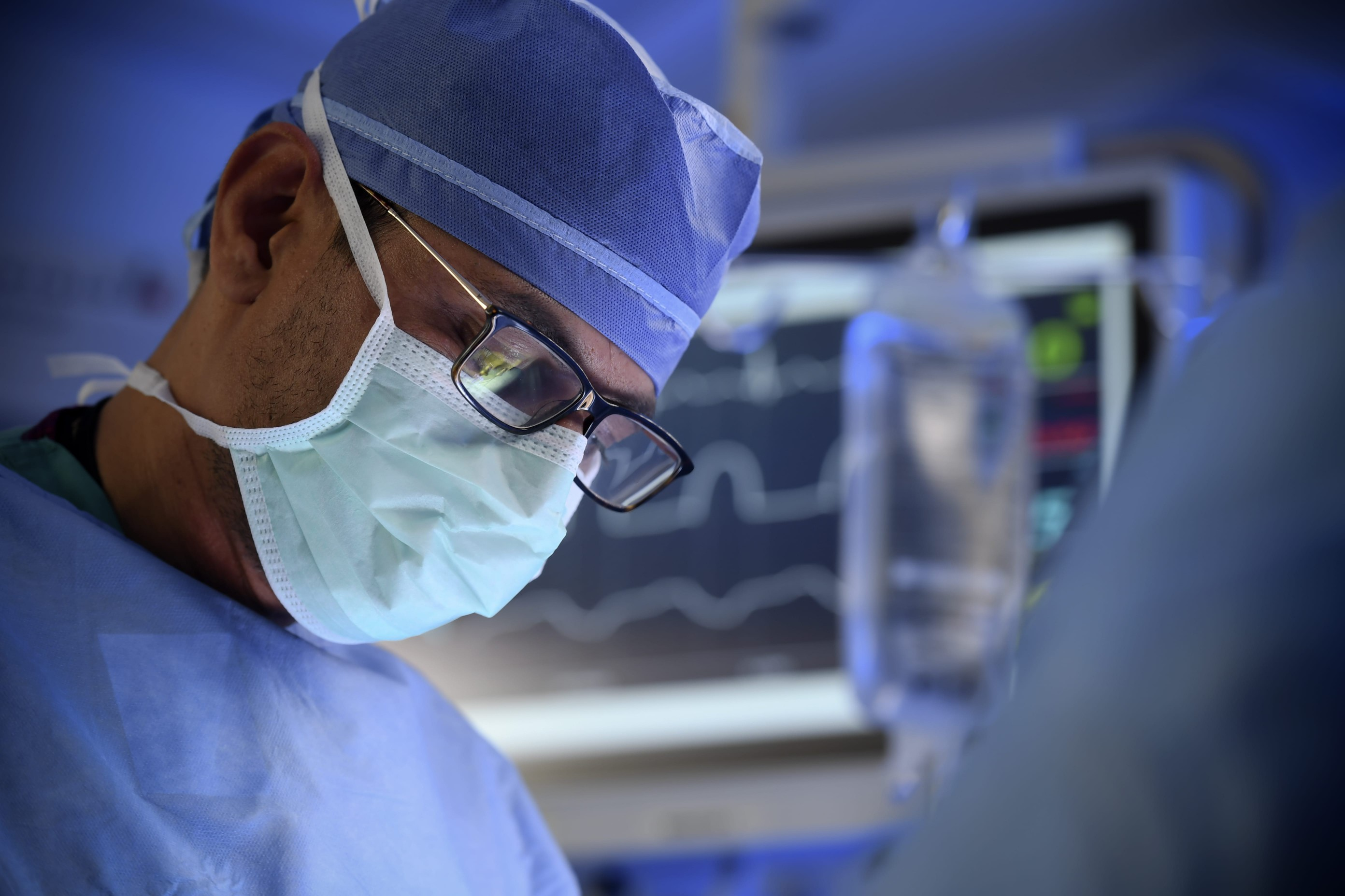 A surgical oncologist in operating attire performs a clinical trial procedure to treat a lung cancer patient