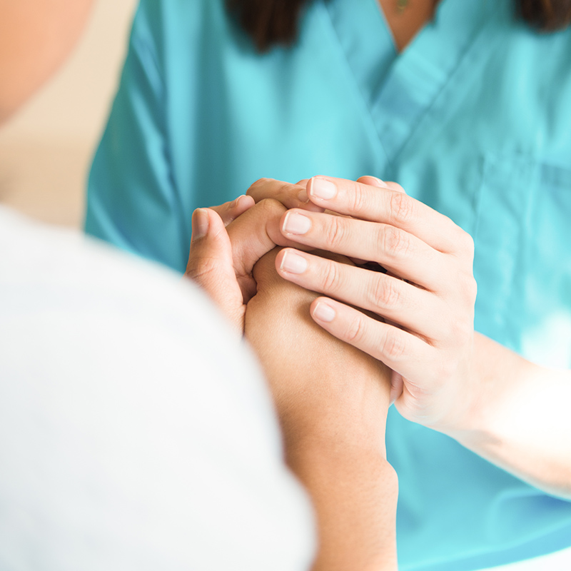 A patient holding a nurse's hand for support