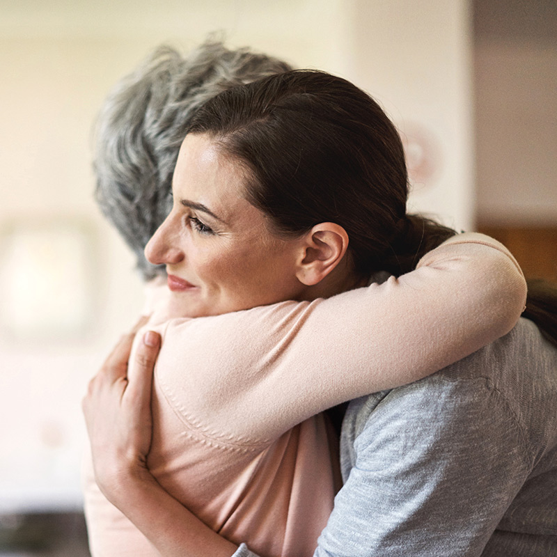 Woman hugging elderly woman