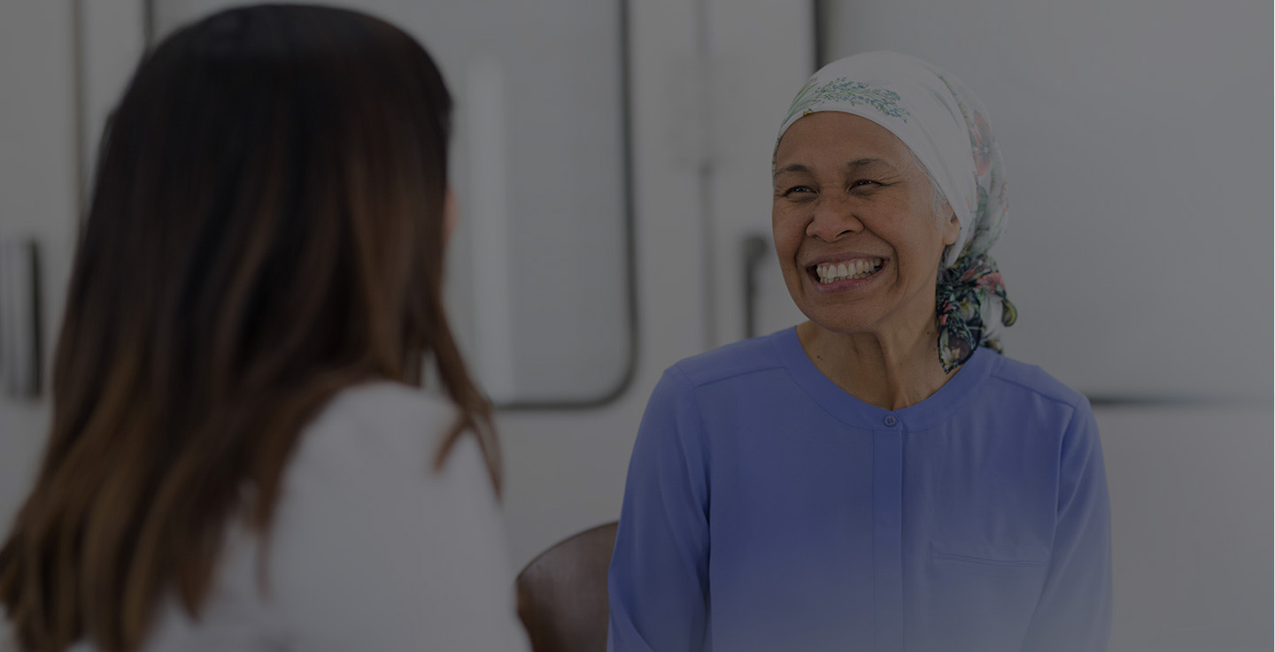 A chemotherapy patient and a cancer treatment specialist smiling